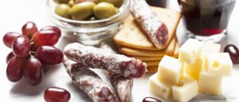 Red wine with charcuterie and grapes and olives