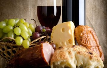 Breads, meat, cheese, with grapes in a basket and a tall wine glass